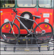 A red bus with a bike rack on the front, holding a bicycle