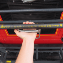 A hand, gripping and squeezing the handle of a bus bike rack to release and open it