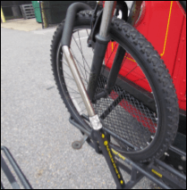 A bicycle with it's tire secured in a bus bike rack by the support arm of the rack