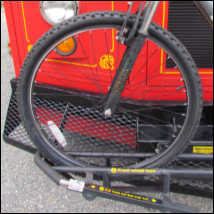 Left side of a bus bike rack with a bicycle placed in to show correct tire placement